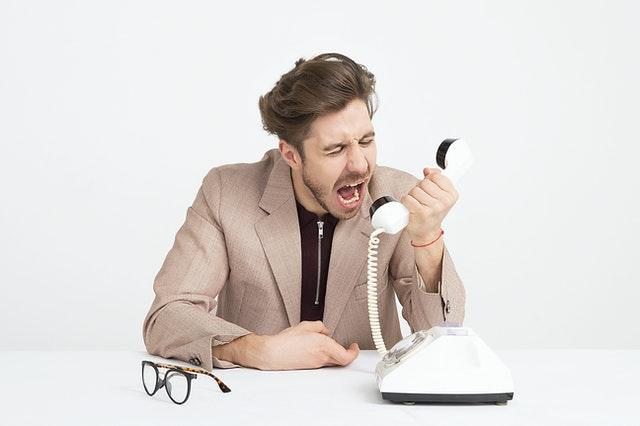 man wearing brown suit jacket mocking on white telephone 1587014 1